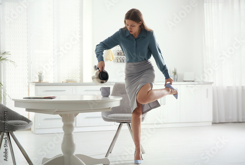 Fototapeta Young woman pouring coffee into cup while putting on shoes at home in morning obraz