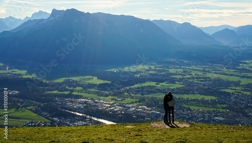 Photo  Couple kiss at the top Untersberg mountain and background with aerial panorama of Salzburg in Austria