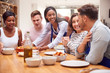 canvas print picture - Group Of Friends Sitting Around Table Eating Meal At Home Together
