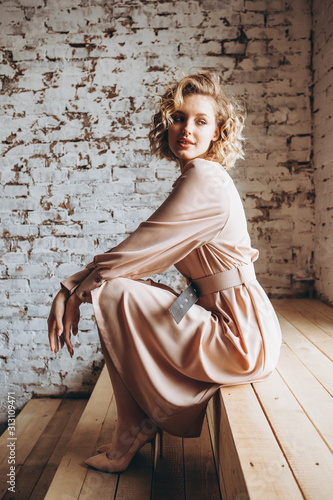 Fototapeta  Portrait of an attractive curly blonde woman poses for the advertisement of a wo