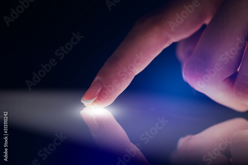 Valokuvatapetti Finger touching tablet with dark background with copyspace