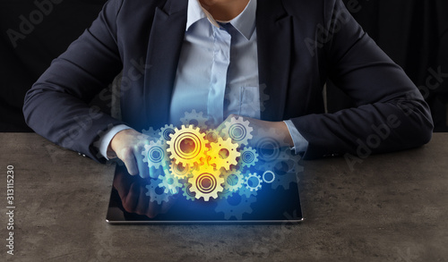 Business woman working on tablet with setting and gear concept