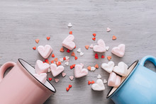 Two Mugs Of Blue And Pink Lie On Their Side, Small Candy Hearts And Marshmallow Hearts Spilled Out