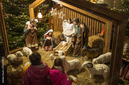 Photographie Czestochowa, Poland, January 1, 2020: Children in front of the Christmas stable