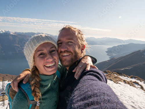 Couple on mountain top taking selfie to celebrate achievement Canvas Print
