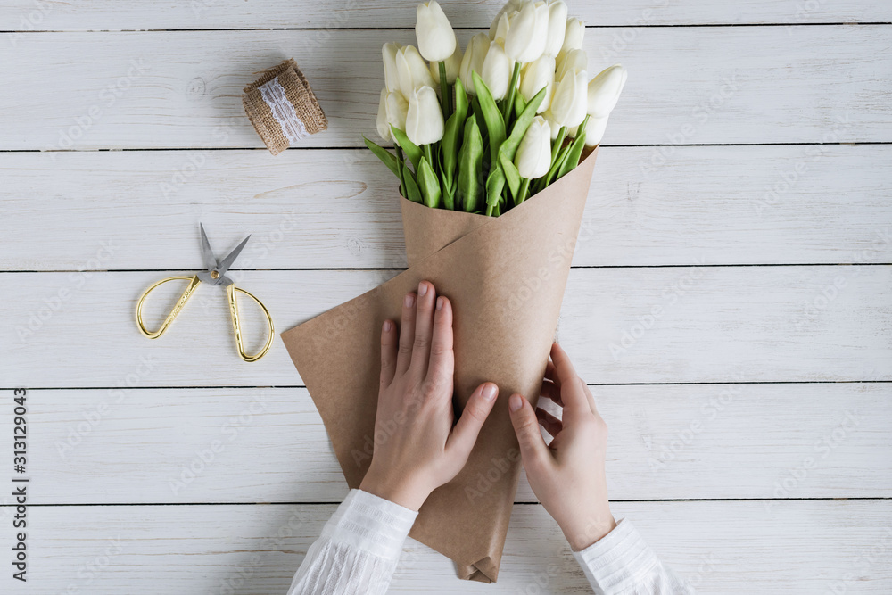 Fototapeta Woman florist wrapping beautiful bouquet of white tulips in pack craft paper on the wooden table. Flat lay