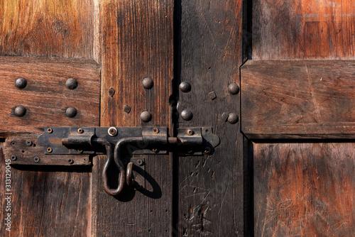 Old lock on wooden door Close-up padlock on old wooden door.