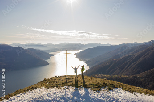 Young couple hiking in Switzerland standing above lake Maggiore arms wide open Wallpaper Mural