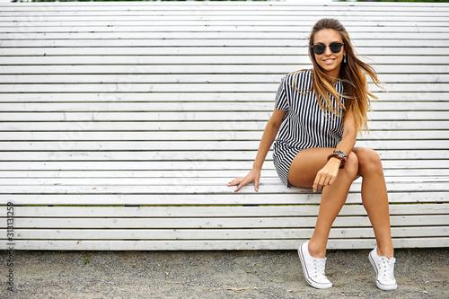 Canvastavla Stylish beautiful girl sitting on a bench
