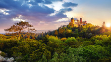 Sintra, Portugal. National Park With Palace Of Pena. Sunrise Among Green Trees Of Forest With Pine-trees And Stones. Panoramic Summer View At Palace With Sunlight And Clouds On The Sky.
