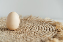Minimalism, One Chicken Egg On A Light Background And A Straw Napkin