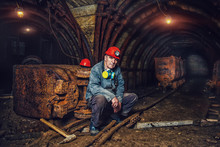 An Elderly Man Dressed In Work Overalls And A Hard Hat Is Standing Near The Old Caravan. Mine Worker. A Tired Miner In A Coal Mine Looks At The Light. Work In A Coal Mine. Portrait Of A Miner.