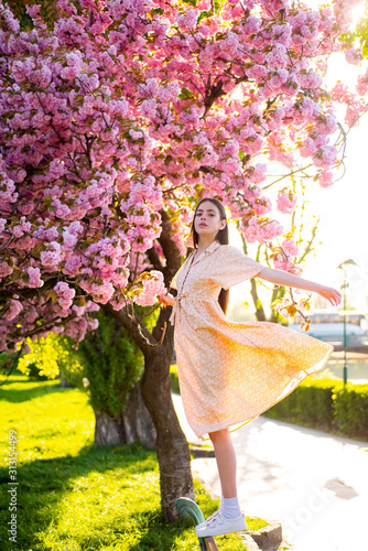 Fotomural  Beautiful young stylish woman walking in sakura park and enjoy beauty of pink flowers