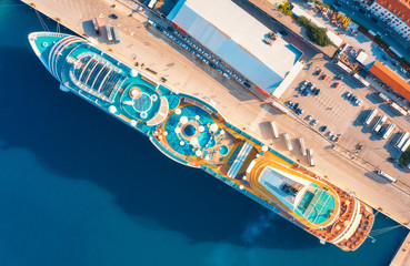 Aerial view of luxury cruise liner in port. Top view of swimming pool with sunbeds, umbrellas and deck chairs, wooden deck on the cruise ship, cars and buildings in summer. View from above. Resort