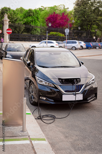 Obraz Electric Car Charging station at Vienna in Austria. Battery hybrid vehicle eco charger. Future energy power. Green technology. Transport and plug. Fuel recharge. Clean ecology concept. Modern supply - fototapety do salonu