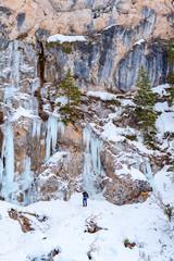Fototapeta na wymiar man walks on frozen lake Braies in Italy in winter, concept of winter travel
