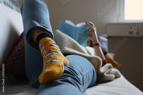 Obraz girl in funny socks lies on a sofa reading a book at home, relaxation and comfort - fototapety do salonu