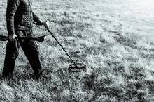 Man On A Treasure Hunt With A Metal Detector In The Woods On The Field