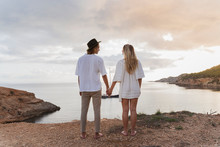 Back View Of Young Couple In Love Standing In Front Of The Sea