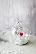 Close Up Of Glass Christmas Bauble With Angel Figurine Inside And Red Heart
