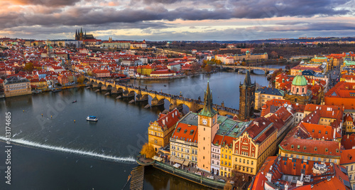 Obraz Prague, Czech Republic - Aerial panoramic drone view of the world famous Charles Bridge (Karluv most) and St. Francis Of Assisi Church with a beautiful winter sunset. St. Vitus Cathedral at background - fototapety do salonu