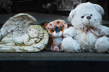 Baby Tombstone In The Cemetery. Angel And Plush Toys (concept: Death, Loss).