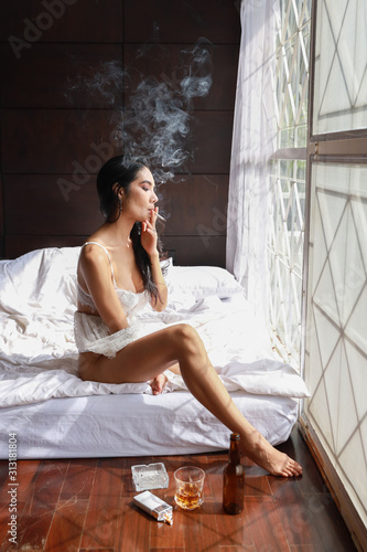 Vászonkép full length drunken asian woman in white lingerie, drinking and smoking while ho