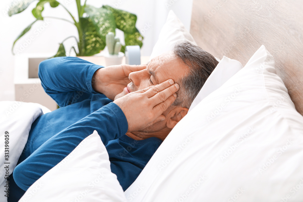 Fototapeta Mature man suffering from head ache while lying in bed