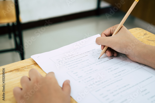 Fotografia English exams test student in school, university students holding pencil for testing exam writing answer sheet or exercise for taking in assessment paper on table classroom