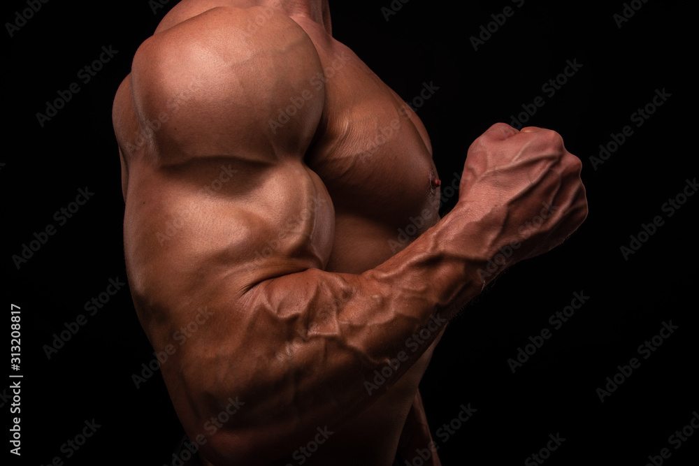 Fototapeta Muscled male model flexing biceps
