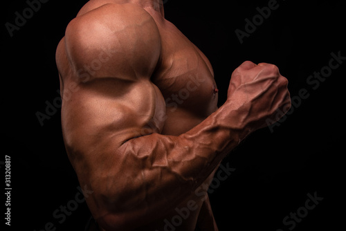 Fotografering Muscled male model flexing biceps