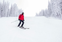 Skier Skiing Downhill In High Mountains During Winter Season