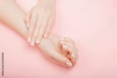 Fotografiet Stylish trendy manicure nail young woman hands on pink background, top view