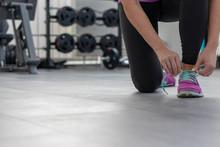 Frau In Sportbekleidung Schnürt Sportschuhe Auf Dem Dunklen Boden Eines Fitnessstudios Mit Gewichten