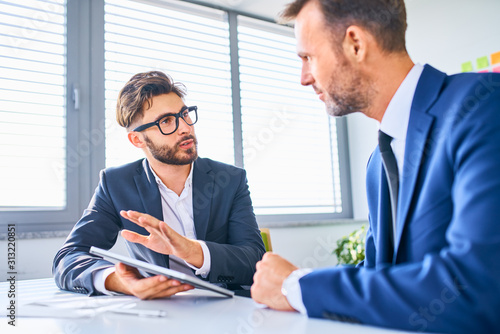 Two businessmen discussing in office standing by the table - 313220851
