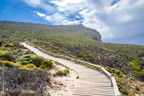 Wooden walkway leading through fynbos vegetation and to the old lighthouse of Ca Fototapeta