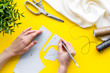 canvas print picture - Tailor working. Women hands drawing patterns for clothes on yellow background top-down
