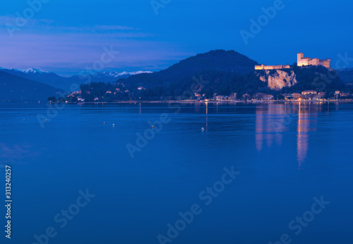 Fototapeta  framed by the snow-capped Prealps, the Angera fortress dominates Lake Maggiore i