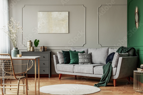 Obraz Stylish emerald green and grey living room interior design with abstract painting on the wall - fototapety do salonu