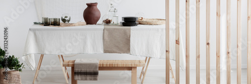 Fotografia White linen tablecloth and clay jug on the table in natural eco dining room