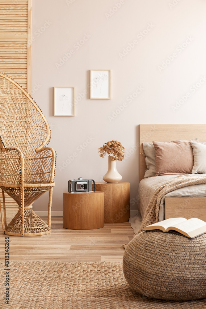 Fototapeta Open book on beige pouf in simple bedroom interior with peacock chair and single bed