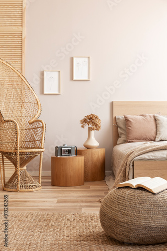 Obraz Open book on beige pouf in simple bedroom interior with peacock chair and single bed - fototapety do salonu