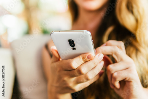 Fototapety, obrazy: using smart phone in vintage cafe Closeup image of a woman hands holding ,