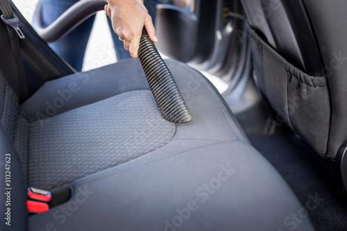 Woman vacuum cleaning car seats
