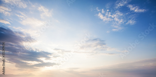 Blue sky clouds background. Beautiful landscape with clouds and orange sun on sky - 313249656