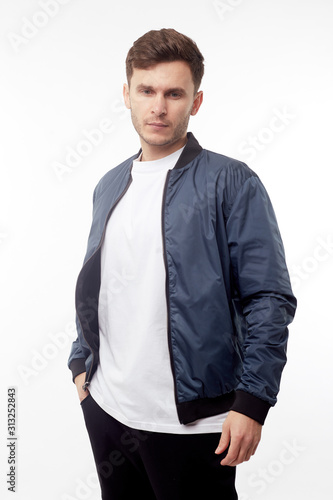 Young european man in white sweater and black pants, blue bomber jacket posing on white background Fototapet
