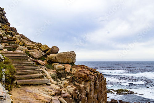 Hiking trail at the coast of Cape of Good Hope with steep cliffs and a rough sea Fototapet