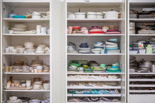 Photo Kitchen cupboard with many plates and bowls