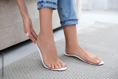 Obraz Woman fitting orthopedic insole at home, closeup - fototapety do salonu