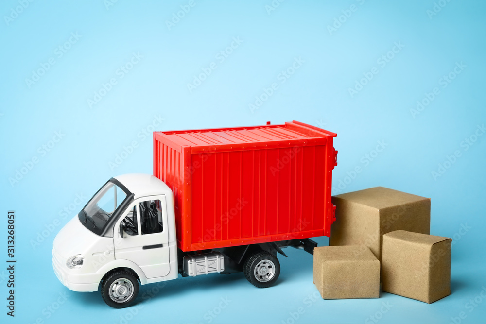 Fototapeta Toy truck with boxes on blue background, space for text. Logistics and wholesale concept